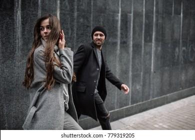 Schönes Paar in stylischen Kleider in grauen Tönen, Stadt