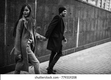 Casal bonito em roupas elegantes em tons de cinza, cidade