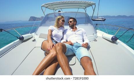 Beautiful couple sunbathing in a yacht