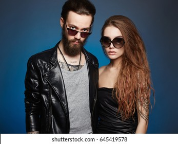 beautiful couple in sunglasses.bearded Hipster boy and beauty girl with tattoo over blue background