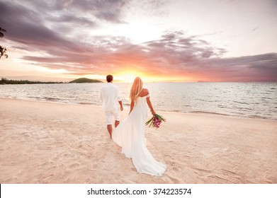 beautiful couple at sunset near the ocean.Honeymoon romantic couple in love holding hands walking on beautiful sunset at beach. Lovers or newlywed married young couple by the sea. Wedding in Thailand.