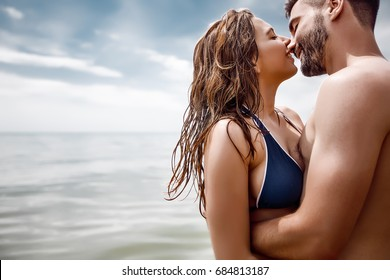 Beautiful couple in swimwear.Couple kisses at sea beach.love concept,happy couple at summer,having fun at tropical beach,enjoy vacations,trendy swimsuit,happiness,relations,summer day,tan,body care