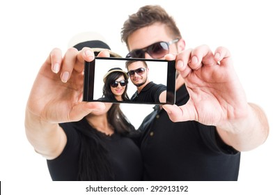 Beautiful couple taking a selfie with smartphone on white background