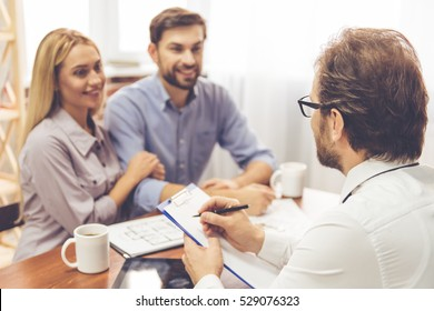 Beautiful couple is talking with handsome realtor, who is making notes