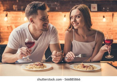 Beautiful couple is talking and smiling while having a romantic dinner together in the kitchen