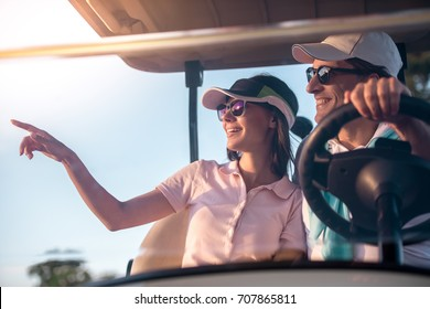 Beautiful couple is talking and smiling while driving a golf cart