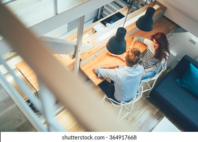 Beautiful couple talking in their pristine home while sitting at kitchen counter