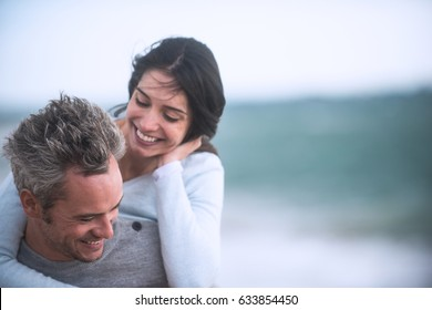 A beautiful couple in their forties walks on the beach, the man wears the woman on his back, they wear sweaters and jeans