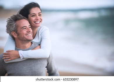 A beautiful couple in their thirties walks on the beach, the man wears the woman on his back, they wear sweaters and jeans
