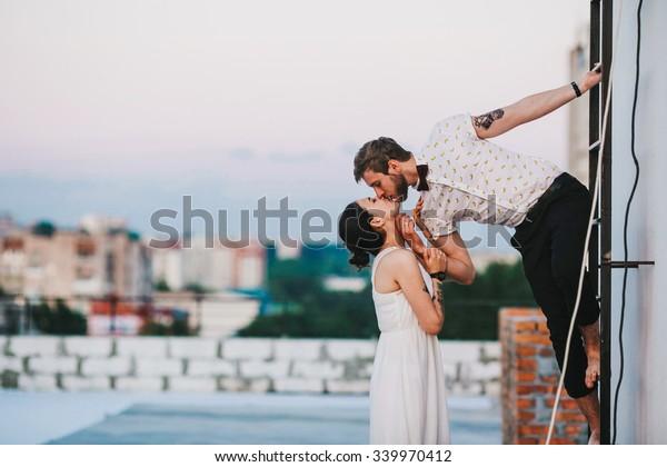 schönes Paar auf dem Dach eines hohen Gebäudes