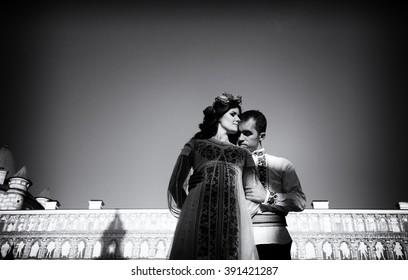 Beautiful couple in traditional Ukrainian dress posing in old town b&w