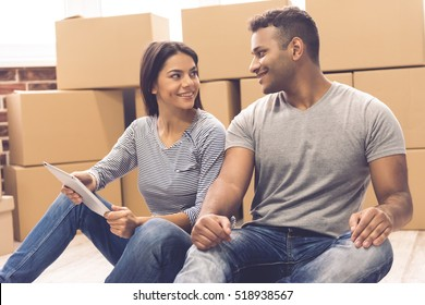 Beautiful couple is using a digital tablet, talking and smiling while sitting on the floor near the moving boxes