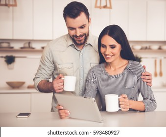 Beautiful couple is using a digital tablet, holding cups and smiling while sitting in kitchen at home