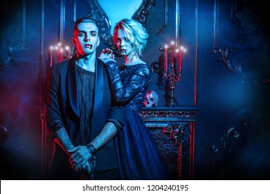 A beautiful couple of vampires is standing in interior. Classic style. Beauty, fashion.