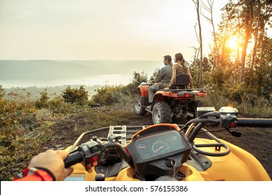 Beautiful couple is watching the sunset from the mountain sitting on ATV