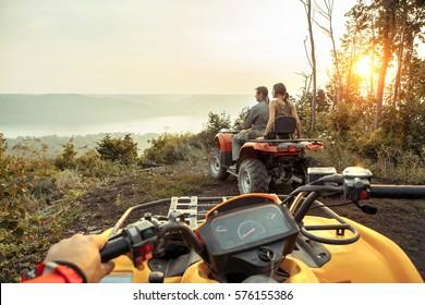 Belo casal está assistindo o pôr do sol da montanha sentado no ATV