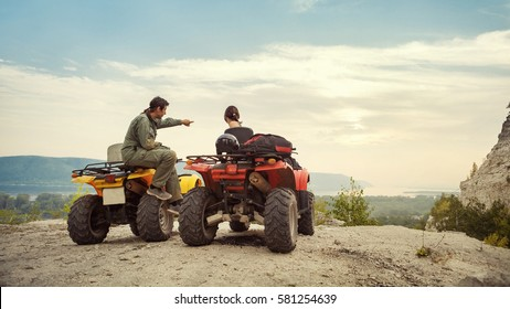 Beautiful couple is watching the sunset from the mountain sitting on quadbike