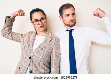 Beautiful couple wearing business clothes showing arms muscles smiling proud. fitness concept.