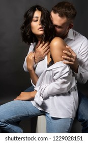 Beautiful couple wearing white shirts and jeans are sitting on a white cube. Man passionately hugs a girl whose shoulder is bare. Casual style. Lifestyle, fashion, commercial design. Gray background.