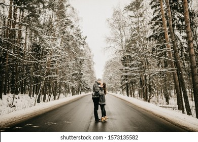 Beautiful couple in winter clothes walking along snowy forest