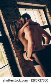 Beautiful couple of young brunet bearded macho guy and curly gorgeous brunette lady, almost naked, are kissing passionately at hotel room, leading brick wall, hot prelude, wild desire