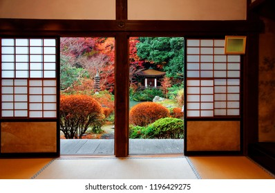 A beautiful courtyard garden with a Japanese pavilion among maple trees viewed from inside a traditional Japanese room with sliding screen doors (shoji) and a tatami floor, in Bishamondo, Kyoto, Japan