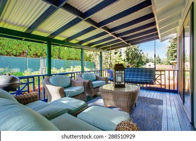 Beautiful covered back deck with chairs and bench swing.