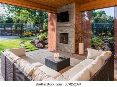 Beautiful covered patio with television, fireplace, and couch, behind new luxury home
