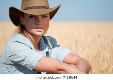 Beautiful cowboy woman with perfect hair and skin posing in country wheat field