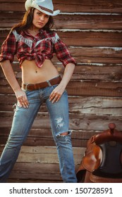 beautiful cowgirl style model posing with saddle on farmland