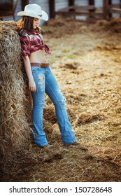 beautiful cowgirl style model posing near hay