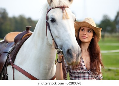 Beautiful cowgirl taking her horse for a ride