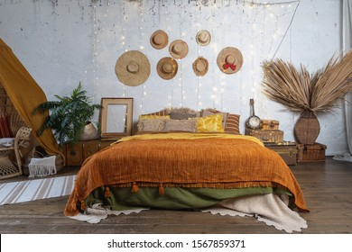 Beautiful cozy bedroom with boho style interior, pillows, cushions, green plants in flower pot, bed and house decor on night table and wall