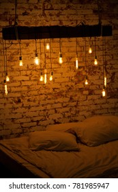 beautiful cozy room in a loft style. bedroom with large bed and white bed linen, and above it the lights are on