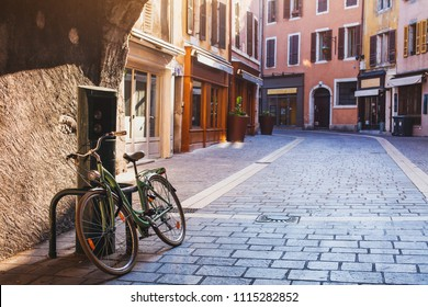 beautiful cozy street in Annecy early morning, France, vintage bicycle on pavement in Europe, european old town cityscape, historical architecture arch passage