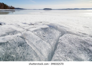 Beautiful and cracked ice at a frozen lake in Finland in the spring.