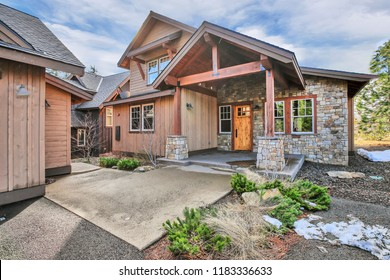Beautiful craftsman home with wood and stone exterior, covered porch and entry columns.