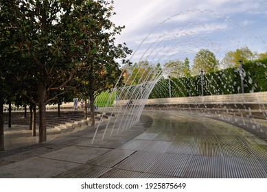 Beautiful Crater Fountain Water in sparkling arc fall on stone. People rest in shade of Evergreen Magnolia Grandiflora near cascading fish pond in Galitsky park. Krasnodar, Russia