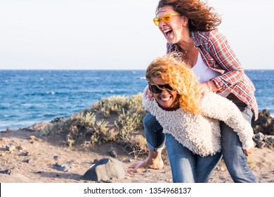 Beautiful crazy caucasian young women carry on eachother having a lot of laughs and fun for friendship - outdoor leisure activity and vacation concept for females friends smiles and gone crazy