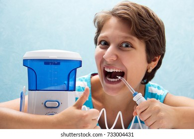 beautiful and crazy girl opened her mouth wide and brushed her teeth with an irrigator with a nozzle for gentle cleaning. Cleaning of teeth with water jet under pressure. girl has short hair.