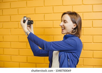 Beautiful crazy girl taking selfie with retro metal film camera on background yellow brick wall.