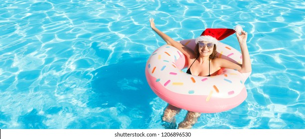 Beautiful crazy woman in christmas hat relaxing on inflatable ring in blue swimming pool. copy space.
