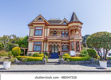 Beautiful cream & butter traditional Victorian house. American Flag hanging over the driveway and shows a garden flowers, lawn and trees. In the background is a beautiful, cloudless, powder blue sky.