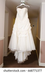 A beautiful cream and clean Wedding dress Hanging in the hall of a hotel room.