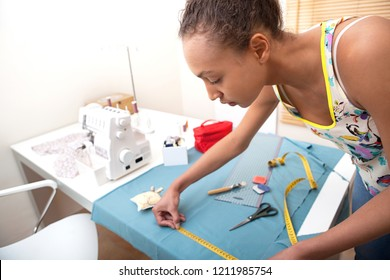 Beautiful creative young fashion design college student using measuring tape, making clothes, interior. Skills and trades, learning focus. Black female seemstress working at home, indoors.