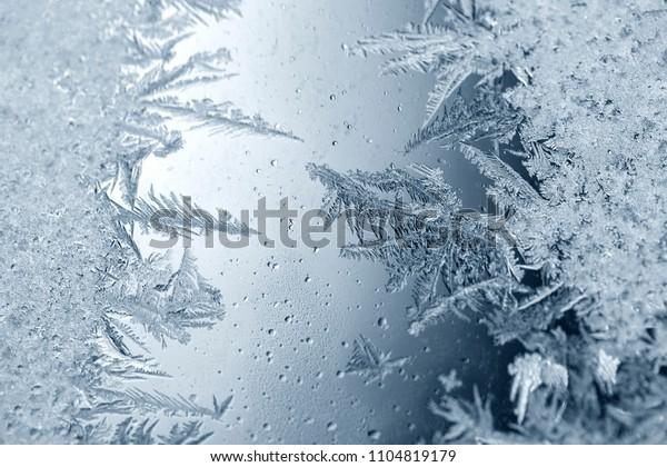 Schöne, knusprige Froststruktur auf einem Fenster mit kaltem blauem Farbverlauf-Licht.