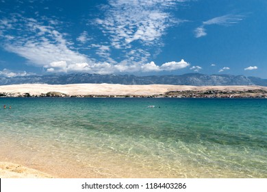 Beautiful croatian beach, mountains in the background and blue water