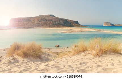 beautiful cross-processed image of Balos Bay at sunset with dry grass and soft sand at foreground, Chania, Crete, Greece