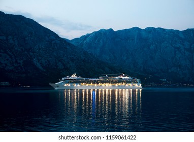 Beautiful Cruise ship at night in the see , mountains in background . Image contains noise