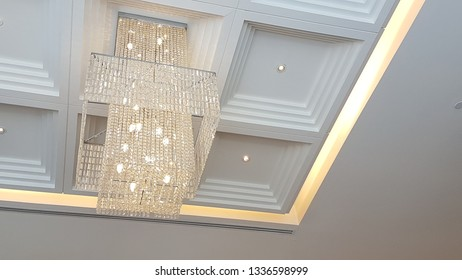 Beautiful crystal chandelier hanging on the ceiling of a luxurious room.